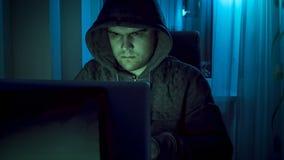Portrait de jeune pirate informatique travaillant sur l'ordinateur portable la nuit photographie stock libre de droits