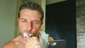 Portrait de jeune salle de bains belle et attrayante d'homme d'intoxiqué d'Internet à la maison avec la serviette sur les dents d image stock