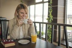 Portrait de jeune tasse femelle magnifique de boissons de café et d'enj image stock