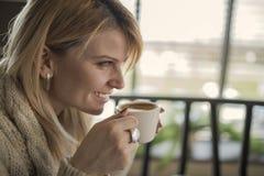 Portrait de jeune tasse femelle magnifique de boissons de café et d'enj photographie stock