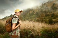 Portrait de jeune touriste féminin avec le sac à dos sur le fond de photo libre de droits