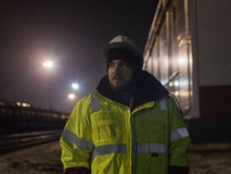 Portrait de jeune travailleur d'entrepôt dans le casque la nuit Image stock