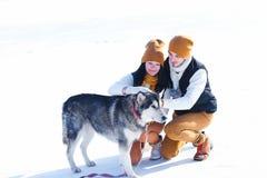 Portrait de jeunes ajouter aux chiens souriant et étreignant en hiver Photos libres de droits
