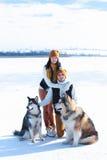 Portrait de jeunes ajouter aux chiens souriant et étreignant en hiver Photos stock