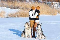 Portrait de jeunes ajouter aux chiens souriant et étreignant en hiver Image libre de droits