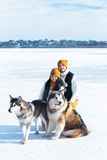 Portrait de jeunes ajouter aux chiens souriant et étreignant en hiver Photo stock