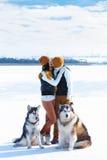 Portrait de jeunes ajouter aux chiens souriant et étreignant en hiver Image stock