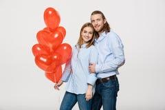 Portrait de jeunes ajouter caucasiens à la mode au coeur de ballons étreignant à l'un l'autre au-dessus du fond blanc d'isolement Image stock