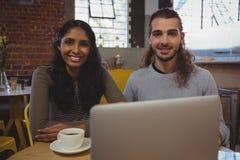 Portrait de jeunes amis avec l'ordinateur portable au café Image stock