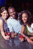 Portrait de jeunes amis ayant des boissons au compteur de barre Photo stock