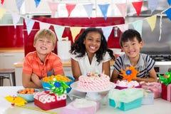 Portrait de jeunes amis célébrant l'anniversaire dans la cuisine Photos stock
