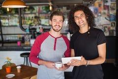 Portrait de jeunes amis de sourire à l'aide du comprimé numérique dans le restaurant Image stock
