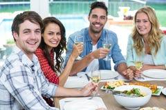 Portrait de jeunes amis de sourire tenant des verres de vin Photos stock