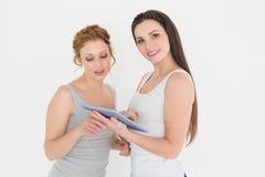 Portrait de jeunes amis féminins occasionnels avec le comprimé numérique Photographie stock