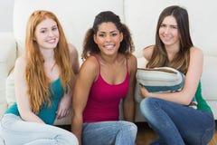 Portrait de jeunes amis féminins sur le plancher contre le sofa Photo libre de droits
