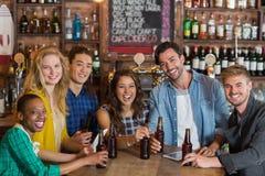 Portrait de jeunes amis gais avec des bouteilles à bière dans le bar Photos stock