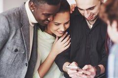 Portrait de jeunes amis gais regardant le téléphone intelligent tout en se reposant en café Personnes de métis dans le restaurant Photographie stock libre de droits