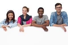 Portrait de jeunes amis heureux avec le conseil vide Photo stock