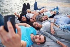 Portrait de jeunes amis heureux sur le pilier au lac Tout en appréciant le jour et faisant le selfie Image libre de droits