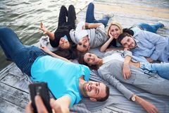 Portrait de jeunes amis heureux sur le pilier au lac Tout en appréciant le jour et faisant le selfie Photo stock