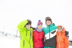 Portrait de jeunes amis se tenant ensemble dans la neige Images stock