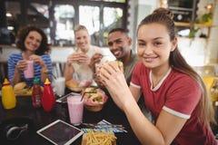 Portrait de jeunes amis de sourire s'asseyant avec la nourriture et la boisson Photo stock