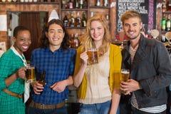 Portrait de jeunes amis tenant des bouteilles à bière Photographie stock