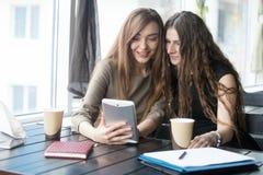 Portrait de jeunes belles femmes regardant l'écran de comprimé dans le Ca Images stock