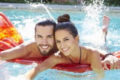 Portrait de jeunes couples détendant dans la piscine Photo libre de droits