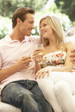Portrait de jeunes couples détendant sur Sofa Drinking Wine Together Photo libre de droits