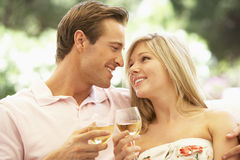 Portrait de jeunes couples détendant sur Sofa Drinking Wine Together Image stock