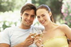 Portrait de jeunes couples détendant sur Sofa Drinking Wine Together Photographie stock
