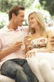 Portrait de jeunes couples détendant sur Sofa Drinking Wine Together Photographie stock libre de droits