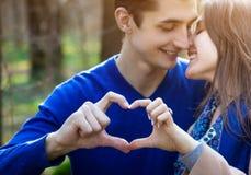 Portrait de jeunes couples d'amour montrant le coeur Photo libre de droits