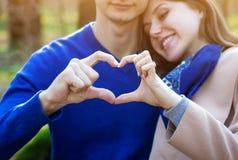 Portrait de jeunes couples d'amour montrant le coeur Photo stock