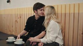 Portrait de jeunes couples dans l'amour à un café, parlant et embrassant Photographie stock