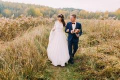 Portrait de jeunes couples de beaux nouveaux mariés flânant dehors Photos stock
