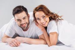 portrait de jeunes couples gais dans l'amour regardant le wile d'appareil-photo se trouvant sur le lit ensemble Images stock