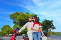 Portrait de jeunes couples heureux d'amour sur le scooter s'amusant Images stock