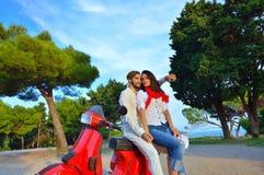 Portrait de jeunes couples heureux d'amour sur le scooter s'amusant Photo stock