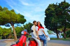 Portrait de jeunes couples heureux d'amour sur le scooter s'amusant Photographie stock