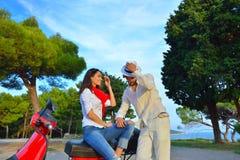 Portrait de jeunes couples heureux d'amour sur le scooter s'amusant Image stock