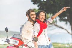 Portrait de jeunes couples heureux d'amour sur le scooter s'amusant en parc à l'heure d'été Photographie stock