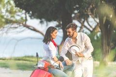 Portrait de jeunes couples heureux d'amour sur le scooter s'amusant en parc à l'heure d'été Photo libre de droits