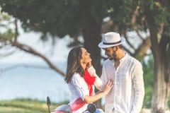 Portrait de jeunes couples heureux d'amour sur le scooter s'amusant en parc à l'heure d'été Photographie stock libre de droits