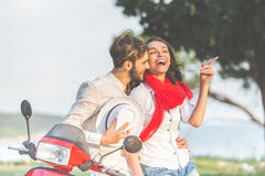 Portrait de jeunes couples heureux d'amour sur le scooter s'amusant en parc à l'heure d'été Photos libres de droits