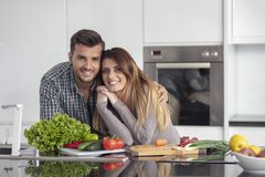 Portrait de jeunes couples heureux faisant cuire ensemble dans la cuisine à la maison images stock