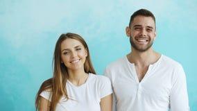 Portrait de jeunes couples heureux souriant et riant dans l'appareil-photo sur le fond bleu Photos stock