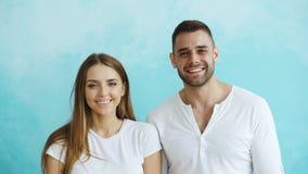 Portrait de jeunes couples heureux souriant et riant dans l'appareil-photo sur le fond bleu Images stock