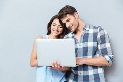 Portrait de jeunes couples heureux utilisant l'ordinateur portable au-dessus du fond gris Photo stock